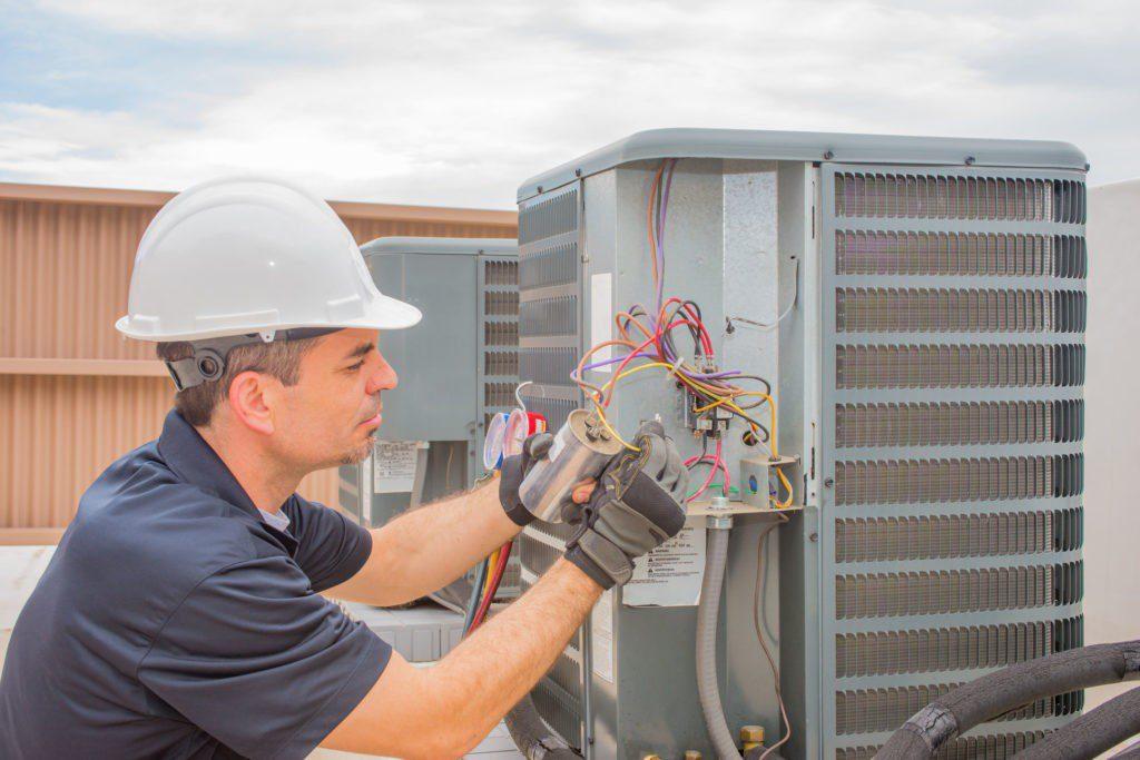 Service Emperor hvac technician checking capacitor on air conditioner