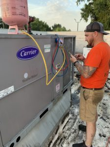Service Emperor owner Tersh Blissett performing an air conditioning repair on a commercial rooftop HVAC unit